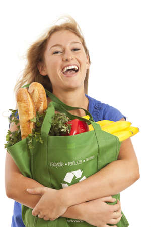 Young woman with green recycled grocery bag of healthy food and vegetables photo
