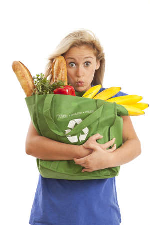 Humorous portrait of young woman with green recycled grocery bag photo