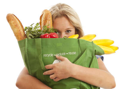 Close-up of young woman with green recycled grocery bag of healthy food and vegetables photo