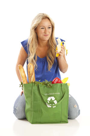 Young woman eating banana from green recycled grocery bag  photo