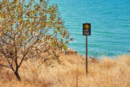 cliff edge: Warning sign cliff edge with a tree Stock Photo