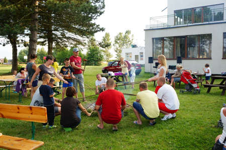 fire place: SIANOZETY, POLAND - JULY 22, 2015: People sitting around a fire place and grilling sausages at a barbecue event