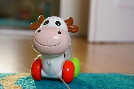 pull toy: Poznan, Polonia - 20 de agosto, 2015: vaca de juguete con ruedas con cable de tracci�n en el suelo Editorial