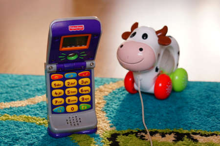 toy phone: POZNAN, POLAND - AUGUST 20, 2015: Fisher Price plastic toy phone and toy cow in background Editorial