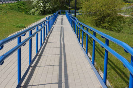 metal handrail: Stone blocks footpath with blue metal barrier