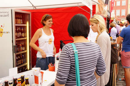 costumers: Woman selling alcohol free beer to pregnant costumers at the Festiwal Dobrego Smaku event in Poznan, Poland