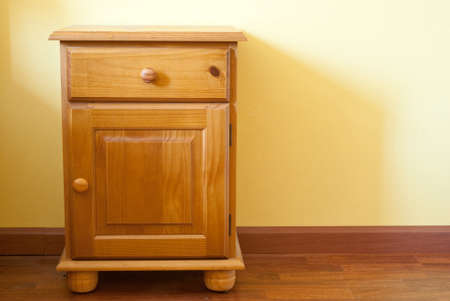 nightstand: A wooden nightstand against a yellow wall Stock Photo