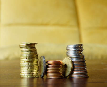 commision: Piles of coins on a wooden table Stock Photo