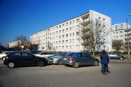 rentals: POZNAN, POLAND - MARCH 13, 2014: Parked cars by apartment buildings