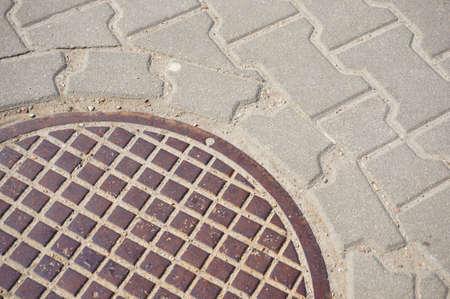 manhole: Round metal manhole by a sidewalk Stock Photo