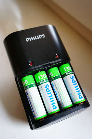 rechargeable: POZNAN, POLAND - JANUARY 01, 2015: Philips Rechargeable batteries in charger