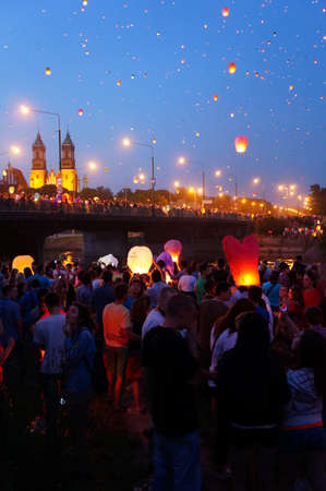 city people: People and sky lanterns on Kupala Night in the city. People celebrate the shortest night of the year on this yearly traditional event.