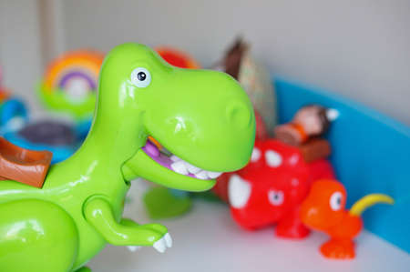 white shelf: Green toy dinosaur on white shelf
