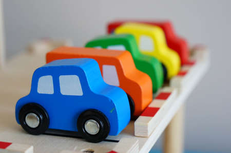 carritos de juguete: Fila de coloridos coches de juguete de madera