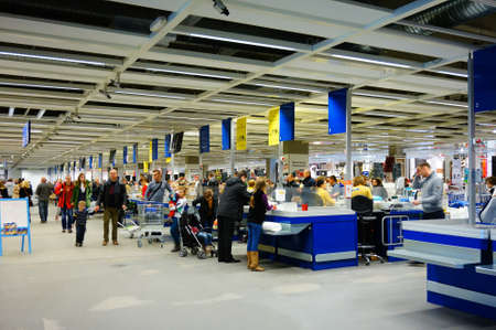 costumers: POZNAN, POLAND - NOVEMBER 24, 2013: Many people at a row of check outs in a Ikea store Editorial