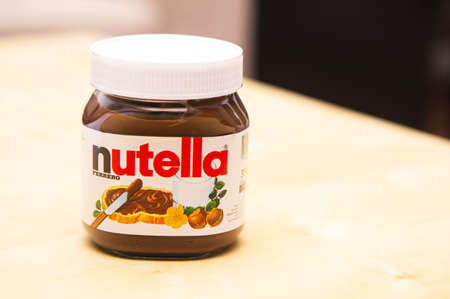 nutella: POZNAN, POLAND - FEBRUARY 10, 2014: Jar of Fererro Nutella hazelnut spread on wooden table