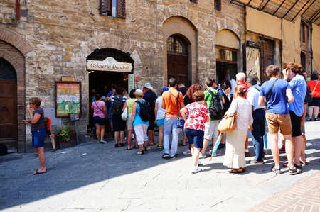 ice cream stand: SAN GIMIGNANO, ITALY - AUGUST 20, 2015: Row of people waiting in front of a Gelateria Dondoli ice cream stand in the city center