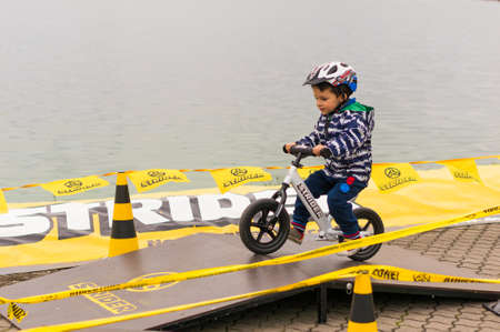 Toddler boy with helmet on a small balance bike riding on a wooden platform along barriers during a Strider Sports show on September 2017 in Poznan, Poland Editorial