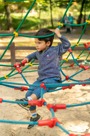 Poznan, Poland - September 16, 2018: Young boy climbing on a rope equipment on a playground at the Solacki park Redakční