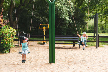 Poznan, Poland - July 29, 2018: Two boy sitting on a swing at a playground in the Cytadela park. It is a warm day in the summer season.