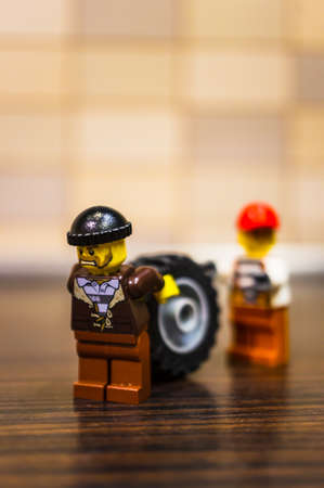 Poznan, Poland - December 18, 2018: Two angry Lego men with hats transporting together a large vehicle wheel in soft focus background. Editorial