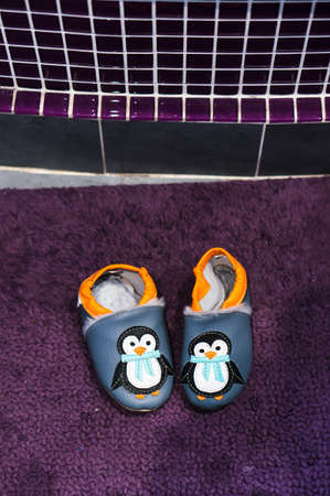 Poznan, Poland - December 20, 2018: Pair of toddler home shoes with penguin next to a mosaic wall.