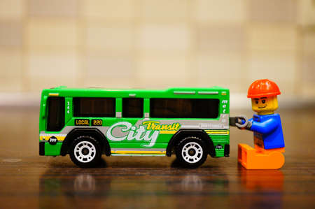 Poznan, Poland - December 22, 2018: Lego construction worker trying to repair a Mattel Matchbox city bus in soft focus background.