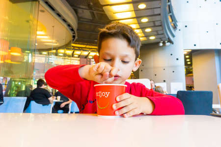 Poznan, Poland - October 13, 2018: Young boy with red blouse eating a ice cream from a paper cup by a table of a ice cream bar in the Stary Browar shopping mall.