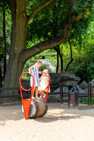 Poznan, Poland - July 29, 2018: Two girls on a spinning equipment on a warm sunny summer day. Playground is located in the Cytadela park. Editorial