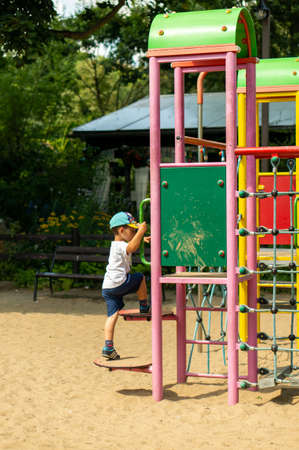 Poznan, Poland - July 29, 2018: Young boy climbing some steps of a equipment on a sunny summer day. Playground is located in the Cytadela park.