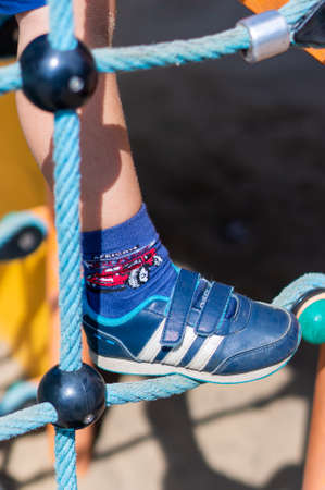 Poznan, Poland - July 29, 2018: Foot of a child with German Adidas brand stripes. Child climbs on a rope of a playground equipment on a warm sunny day.