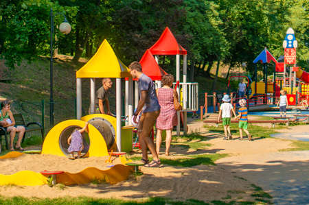 Poznan, Poland - July 29, 2018: Adults watching their playing children at a playground in the Cytadela park