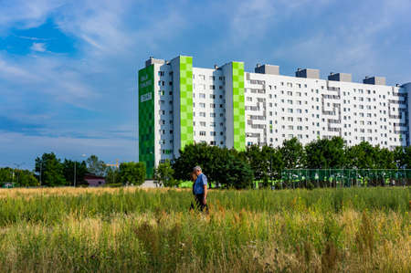 Poznan, Poland - July 10, 2018: Man and woman walking between a field with plants on a sunny summer day in the Orla Bialego district. High renovated apartment block in the background. 写真素材 - 122360004