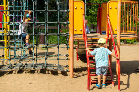 Poznan, Poland - July 29, 2018: Young boys walking on steps and climbing on a rope net of a equipment on a warm sunny summer day. Playground is located in the Cytadela park. Redakční