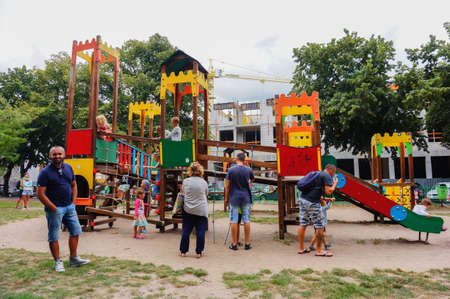 Kolobrzeg, Poland - August 10, 2018: Parents watching their children playing on a equipment with slide at a playground on a cloudy day Редакционное