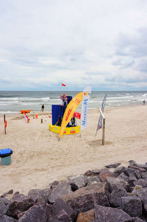 Kolobrzeg, Poland - August 10, 2018: Beach with guard tower showing red flag. It is a cloudy windy day with many waves. Out of safety swimming is forbidden. Coast is almost empty in high season. Editorial