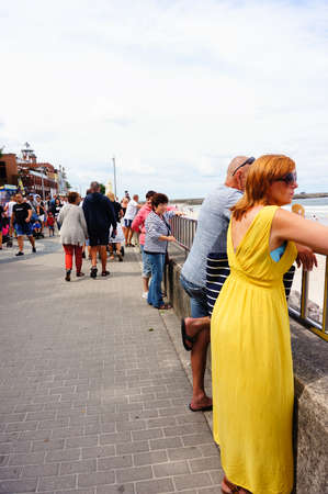 Kolobrzeg, Poland - August 10, 2018: Woman in yellow dress and man standing by a barrier on the crowded promenade watching at the sea. This walk area is build along the beach.