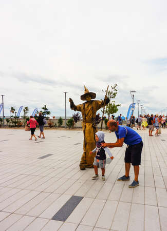 Kolobrzeg, Poland - August 10, 2018: Man and child standing by a person dressed as witch with golden clothes close by the beach on a cloudy day.