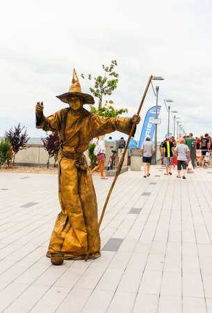 Kolobrzeg, Poland - August 10, 2018: Person dressed as a witch in golden clothes on a square near the beach and a pier. In the high season this place is very crowded.