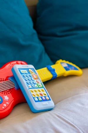 Poznan, Poland - October 10, 2018: Fisher Price toy telephone lying against a toy guitar on a sofa in soft focus Editorial