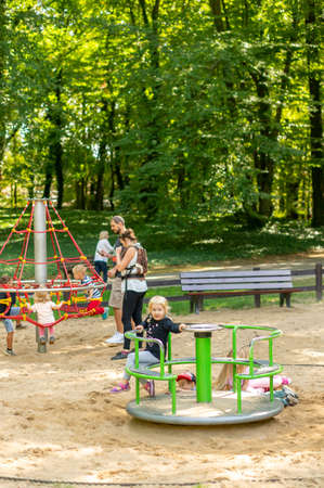 Poznan, Poland - September 16, 2018: Young girl in a roundabout with climb equipment in the background on a playground at the Solacki park