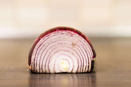 Fresh red onion cut in half on a wooden surface in soft focus background.
