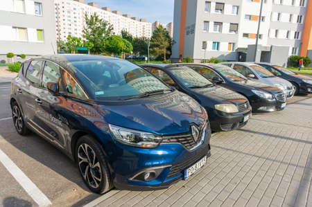 New blue parked Renault Scenic car by a sidewalk close by apartment buildings on the Stare Zegrze district on circa May 2019 in Poznan, Poland.
