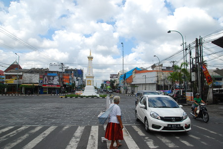 a grandmother crossing the street alone through zebra cros in jogja monument area