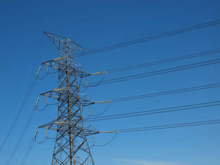 megawatts: High power electricity post with cables in blue sky