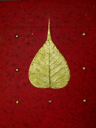 Gold leaf over red background photo