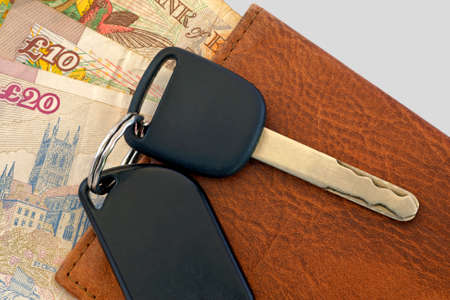 payoff: Car key with remote switch, document cover and english pounds