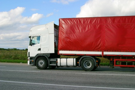 A white truck with red load cover on highway  Imagens