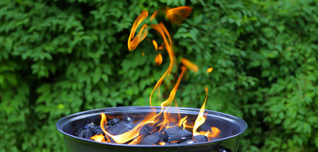 barbecuing: Hot grill pot with flame, preparation for  barbecuing. Stock Photo