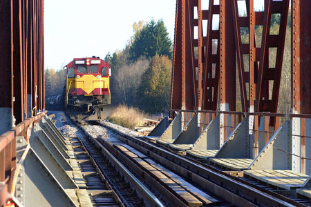 naphtha: Freight train approaching the railway bridge in countryside. Stock Photo